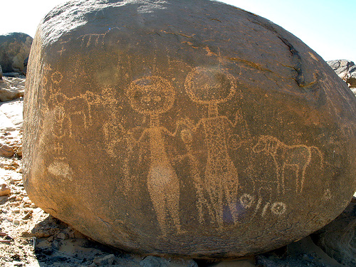 boulder petroglyph of women with arms raised, animals
