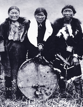 older woman holding drum resting on ground
