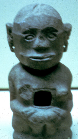 short stone sculpture with big head and vulva, and large hollow between breasts and waist