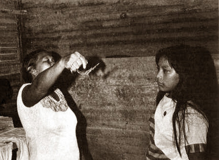 a woman shaman clearing energy from a young woman inside a wooden cabin