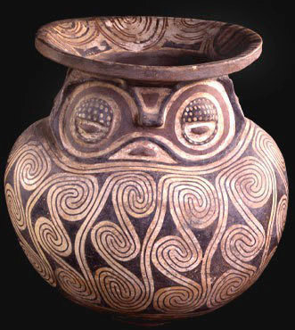 funerary urn with owl face and spiral patterns